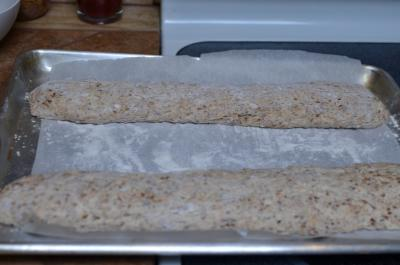 2 raw baguettes placed on a baking sheet lined with parchment paper that is floured