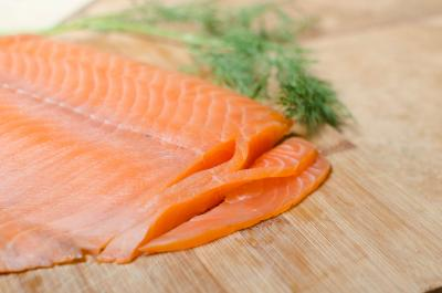 Salmon being sliced into thin, long strips