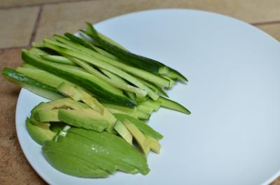 Avocado and cucumber cut into long thin strips and place on a plate