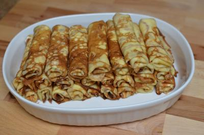 Crepes rolled up and stacked in a bowl
