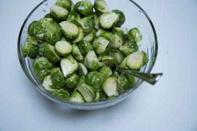 Brussel sprouts, in a bowl, covered with olive oil, salt, pepper, lemon juice and garlic