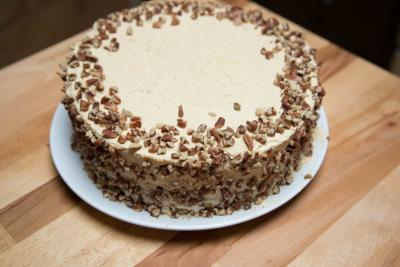 Top of the cake covered with cream and nuts placed on the sides of it