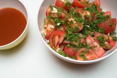Tomatoes with dill and garlic in a bowl and the marinate in a bowl next to them