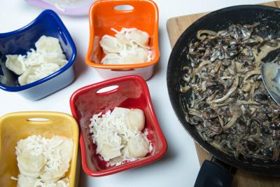 4 ramekins each with dumplings and cheese and the mushroom cream sauce next to them in a skillet