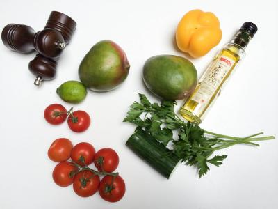 Ingredients on the table including; tomatoes, cucumbers, parsley, 2 mangos, 1 lime, 1 yellow bell pepper, olive oil and salt and pepper