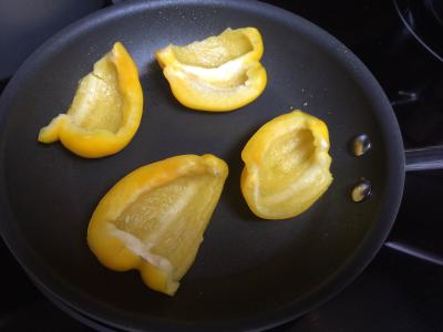 Yellow bell pepper being roasted on a pan