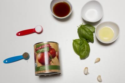 Ingredients on the table including; a can of diced tomatoes, 3 garlic cloves, basil leaves, marsala wine in a bowl, a bowl of olive oil, sugar in a bowl and salt and pepper