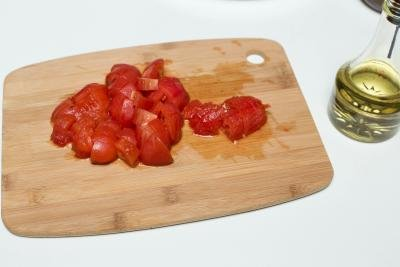 Peeled tomatoes being diced on a cutting board