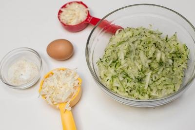 Ingredients on the table including; a bowl of grated zucchini, a little bowl garlic salt, a measuring spoon with mozzarella cheese, a measuring spoon of parmesan, and an egg
