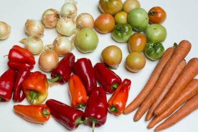 Vegetables on table including carrots, peppers, tomatoes, and onions