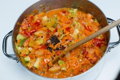 Diced tomatoes and seasoning added to pot with veggies