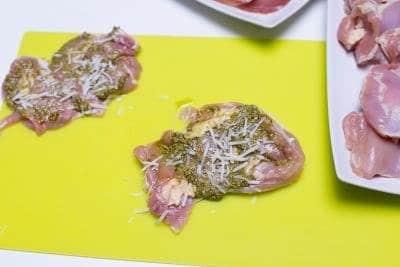 Basil pesto and cheese placed inside the chicken thigh that is laying on a cutting board
