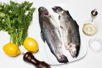 Ingredients on the table including; 2 lemons, parsley and dill, 2 trouts, oil, salt and pepper