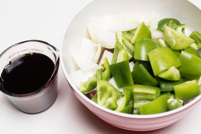 Green bell peppers, onions and lam pieces all combined in one bowl with sauce next to it in a measuring cup