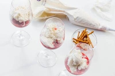 3 wine glasses each with strawberry mixture and ice cream in it