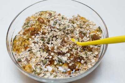 Coconut Granola ingredients being mixed with honey and coconut oil in a bowl