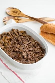 Slow Cooker Beef Roast in a baking pan with bread and 2 wooden spoons next to it