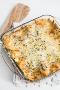 Spinach Dip Lasagna in a baking pan standing on a kitchen towel