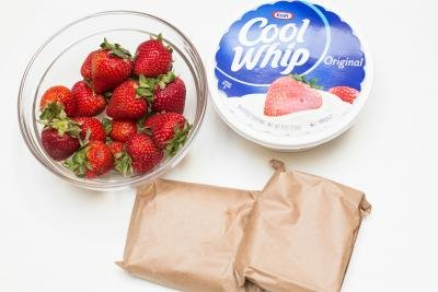 Ingredients on the table including; strawberries in a bowl, cool whip and strawberry jello