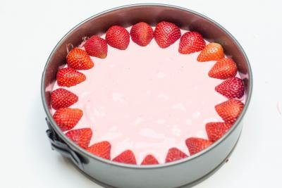 Strawberry halves placed around the circumference of the Strawberry Jello Cake Dessert in the baking pan