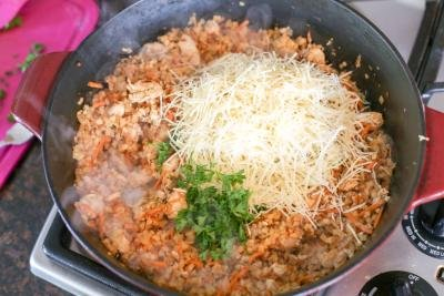 Parmesan added to the cauliflower rice in the iron skillet pot