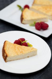 Farmers Cheese Coffee Cake slice on a plate with raspberries besides the slice